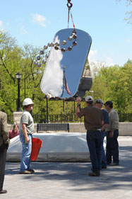 Installation of memorial sculpture, American flag reflected