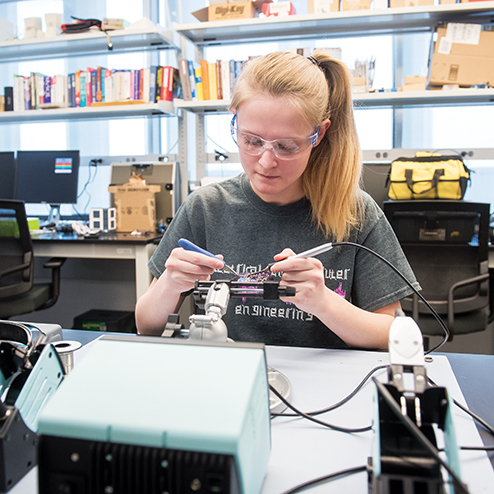 An engineering student works on a piece of equipment in a studio classroom setting.