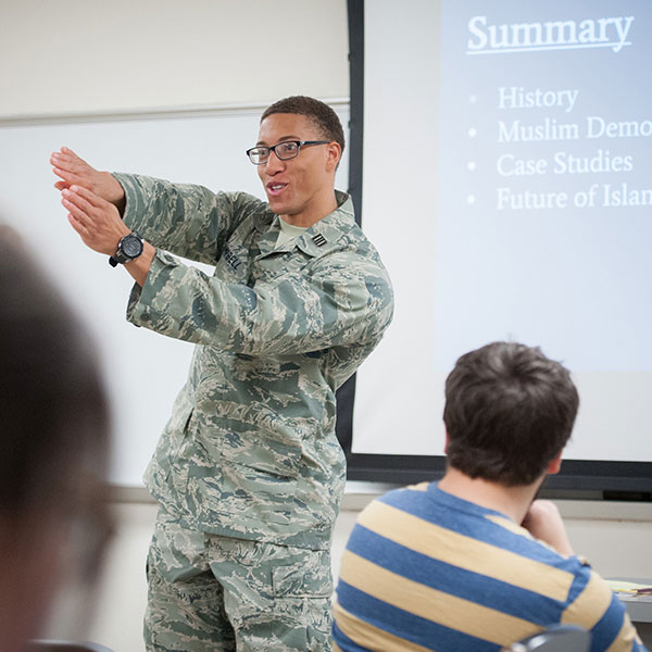 A student in Army fatigues gives a presentation in a political science classroom to his peers.