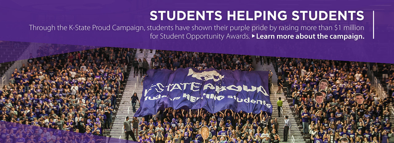 Students at basketball game holding up K-State Proud banner