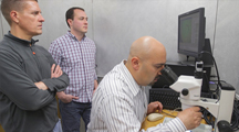 Image of Dr. Brian Geisbrecht overseeing research with lab staff and link to Dr. B. Geisbrecht's YouTube research video