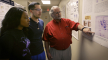 Image of Dr. Kanost discussing research poster with students.