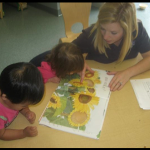 Miss Rene reading a book about seeds to her class. Reading picture books to children about gardening is an enjoyable way to help them learn.