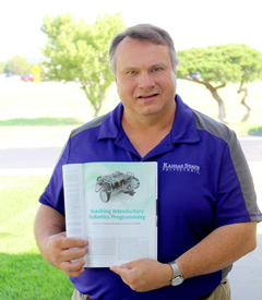 Tim Bower, computer systems technology professor at Kansas State Polytechnic for 12 years, holds his published article on robotics programming for beginners in the IEEE Robotics and Automation magazine.