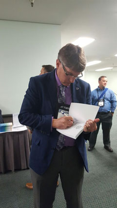 Grant Chapman signs copies of the recently released NAFSA publication