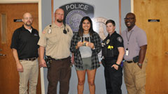 K-State Police Glen Brown, Randy Myles, Samantha Purdy and Jason Blackburn present April Aranda with gift cards.