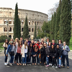The study abroad group poses outside the Colosseum