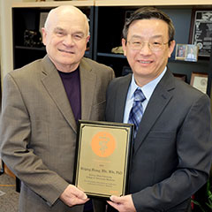 Dr. Franke Blecha presents the Zoetis Research Excellence Award to Dr. Weiping Zhang