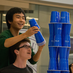 Competing for first place, two students participate in a cup stacking challenge during Hack K-State 2017.