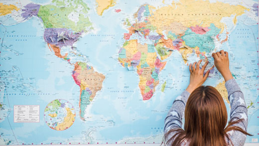 Girl places pin on world map.