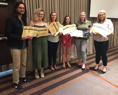 Peter Loganbill, Olivia Bergmeier, Dene Dryden, Paige Eichkorn, Kaylie McLaughlin and Molly Hackett display some of the more than 30 awards won by student publications for their work covering K-State in 2018.