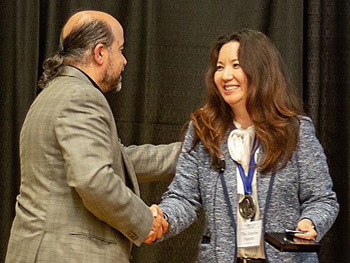 Dr. Annelise Nguyen receives John Doull Award from Dr. James Sacco, 2019-2020 CSSOT President
