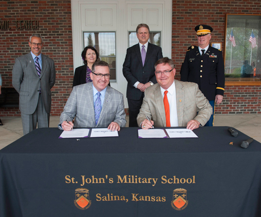 Kansas State University President Kirk Schulz, left, and St. John's Military School President Andrew England sign an institutional partnership agreement that will serve the collegiate needs of St. John's students.