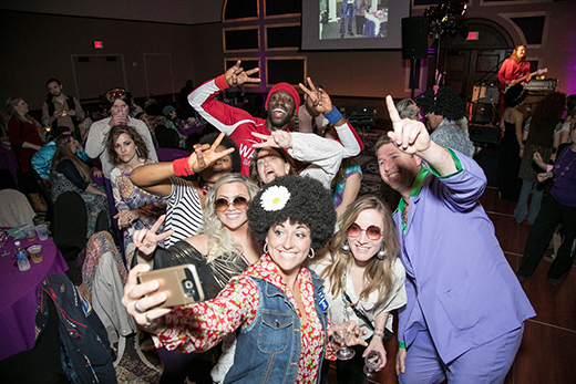 Retro-costumed attendees of the 2017 Pink and Purple Polyester Party.