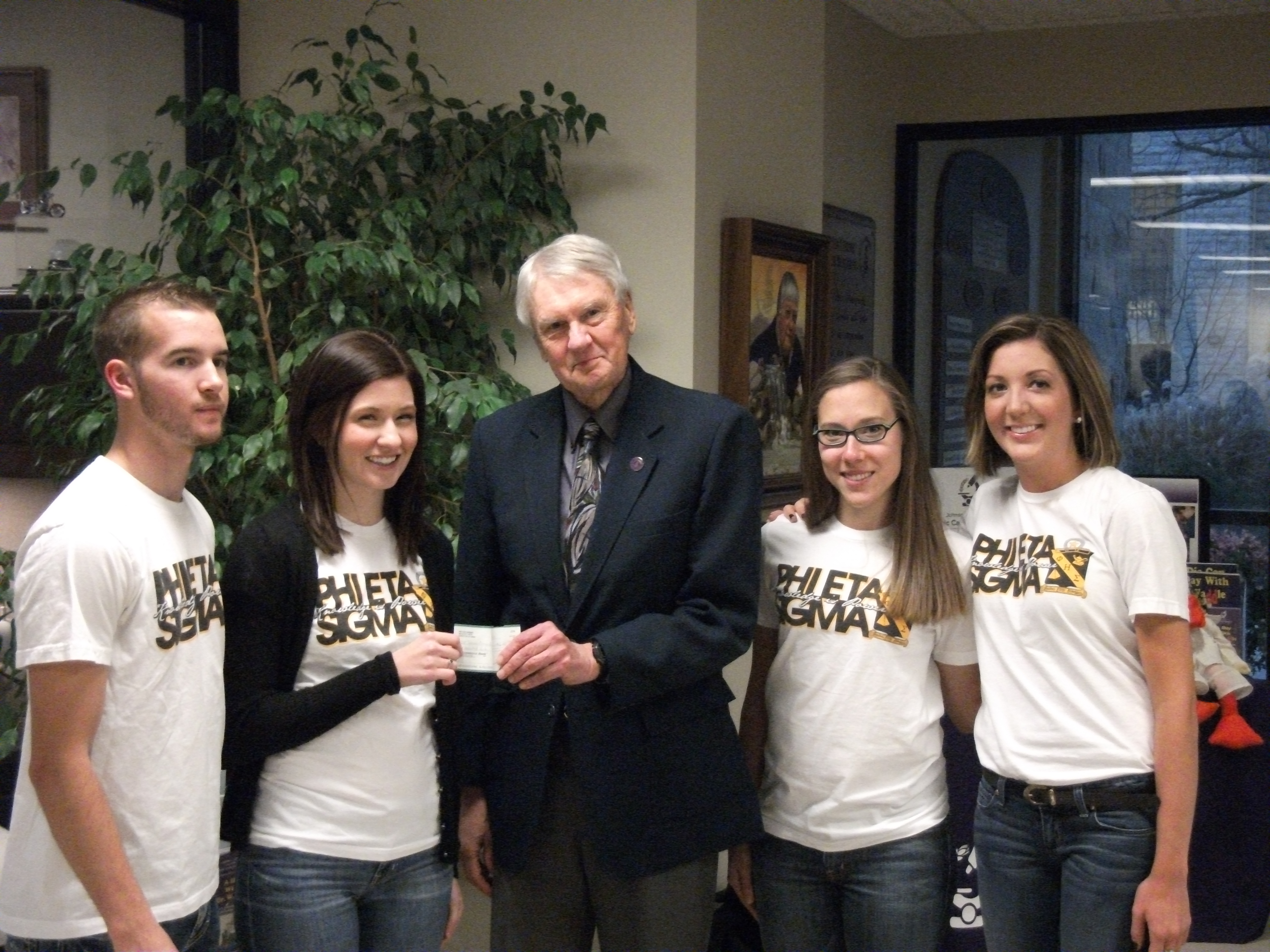 Photo of Phi Eta Sigma Officers Presenting Check