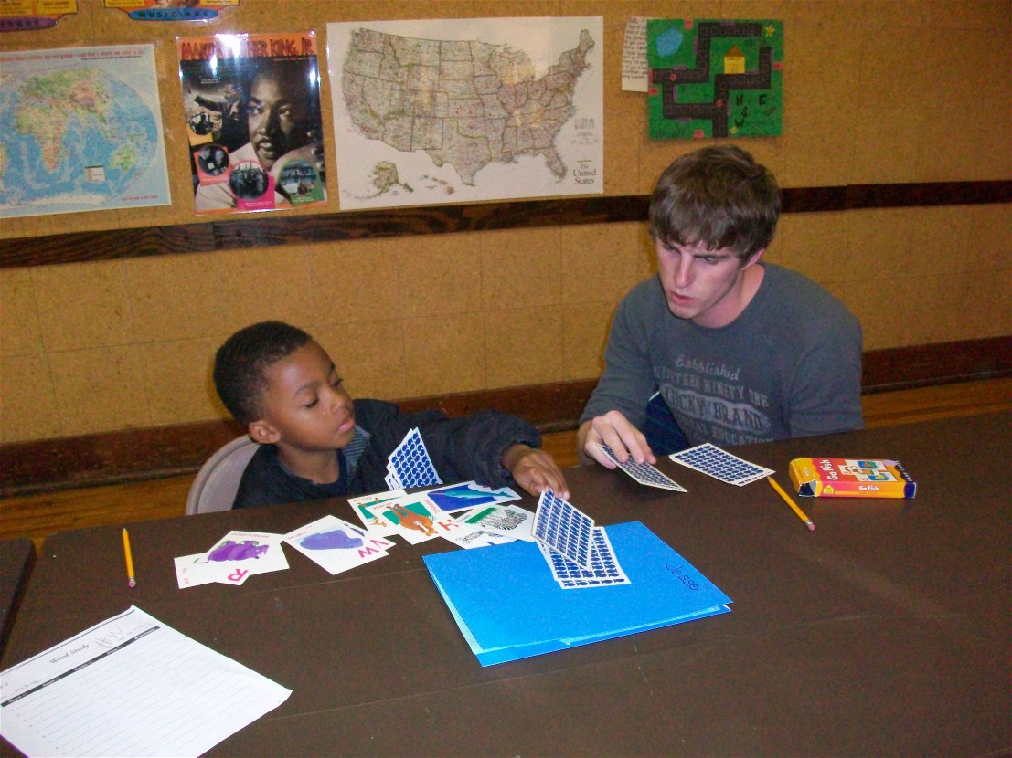 Tyler Link practices flashcards with a student at the Douglass Center.