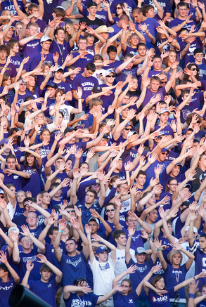 Students wave and cheer at a K-State home football game.